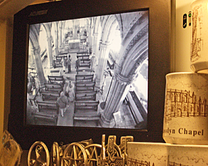 Security TV monitor showing inside of chapel and tourist mugs