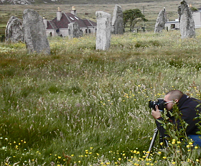 Standing stones, long grass, house in the background, photographer crouched in the foreground