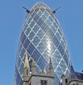 Gherkin-shaped blue building with neo-gothic facade in foreground