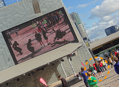 Big screen showing two teenage women surrounded by digital ninjas. Onlookers are also visible.