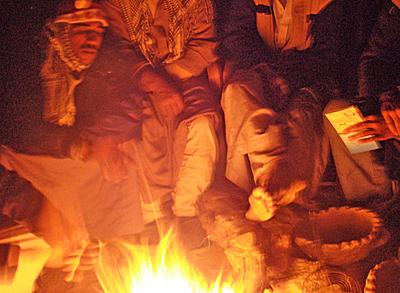 Men round a blazing fire at night