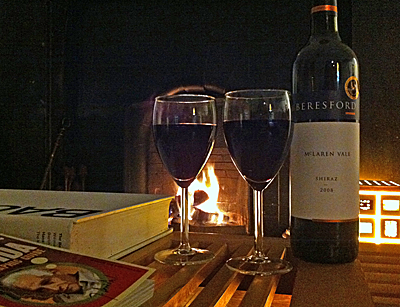 In fact 2 filled red wine glasses and bottle on a coffee table in front of an open fire