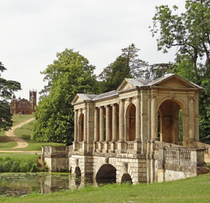 Palladian Bridge, Stowe Park, England: Classical stone bridge over ornamental lake. Path leading to rusticated folly in the background.