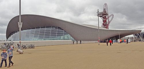Olympic Aquatic Centre, March 2014. Exterior showing sweeping form of the roof; Orbital building in the background; kids and bikes in the foreground