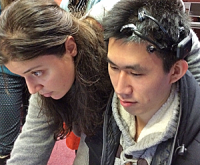 Female and male closeup. The Chinese male is wearing the Emotiv Epoc EEG cap.