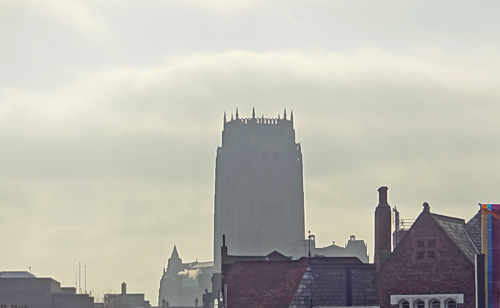 Central tower viewed over rooftops, in the haze
