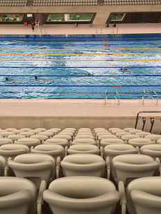Olympic Aquatic Centre, March 2014. Looking down from seating area to the swimming lanes with swimmers; seats look like cream coloured corpuscles